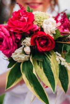 Buquê de casamento com peônias vermelhas e folhas verdes nas mãos da noiva feliz com sorriso