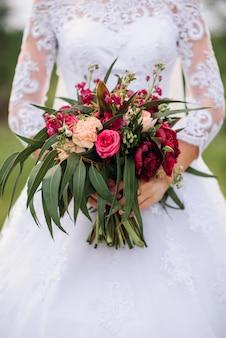 Buquê de casamento com peônias vermelhas e folhas verdes nas mãos da noiva