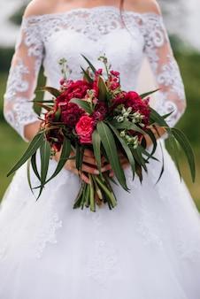 Buquê de casamento com peônias vermelhas nas mãos da noiva em um vestido branco