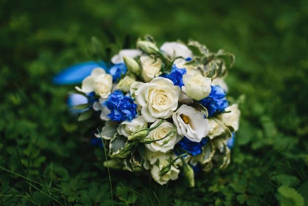 Buquê de casamento com rosas brancas e flores azuis