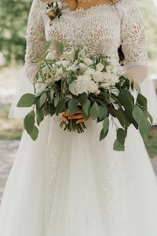 Buquê de casamento com rosas brancas e folhas verdes. noiva de vestido contém buquê.