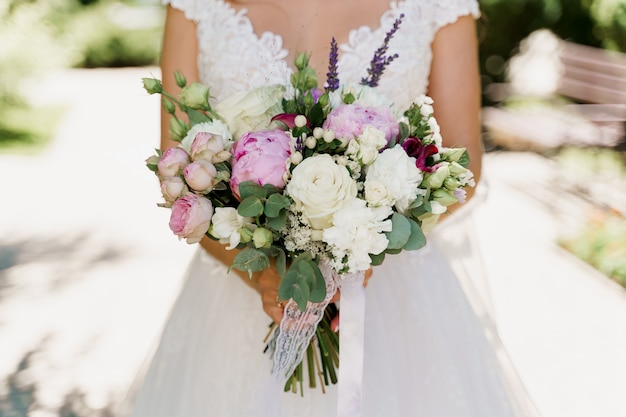 Buquê de casamento com rosas brancas, peônias e folhas verdes. noiva de vestido contém buquê.