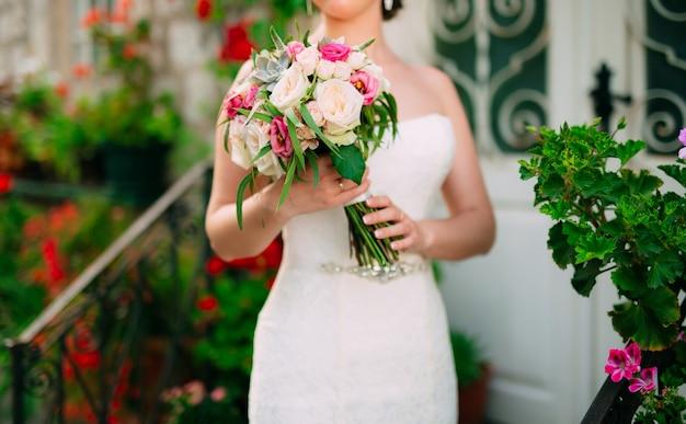 Buquê de casamento com rosas, peônias e suculentas nas mãos