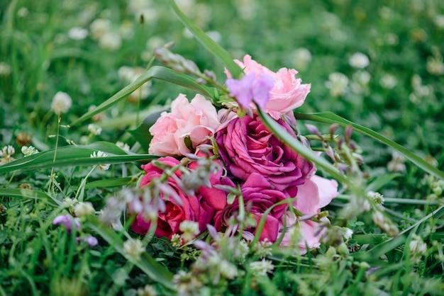 Buquê de casamento com rosas roxas e cor de rosa, violetas flores deitado em uma grama verde