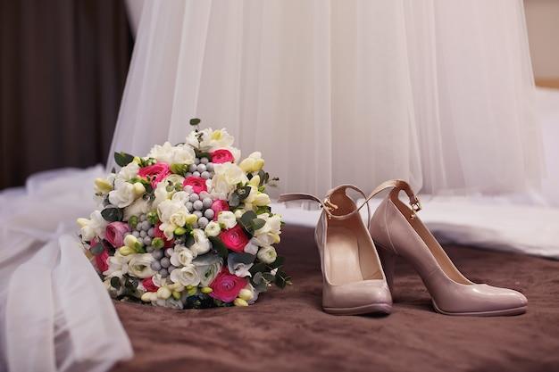 Buquê de casamento com sapatos no quarto da noiva
