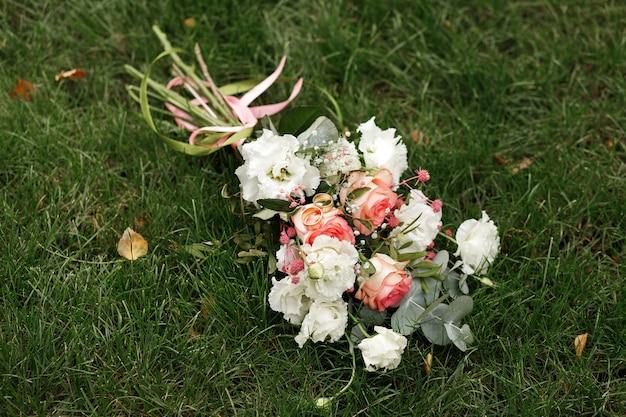 Buquê de casamento da noiva e anéis na grama verde em setembro. acessórios de casamento