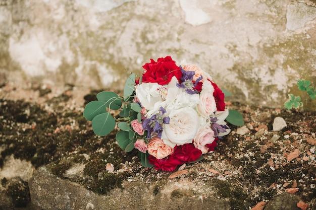 Buquê de casamento da noiva em um fundo de parede de pedra