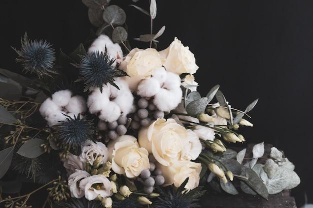 Buquê de casamento de inverno de rosas brancas, algodão e eringium em um preto. o buquê da noiva.