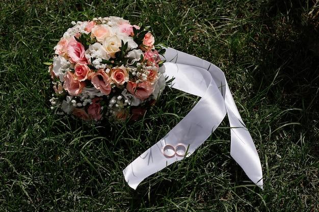 Buquê de casamento e alianças de ouro na grama verde. dia do casamento