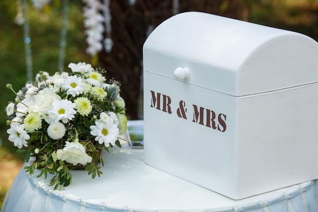 Buquê de casamento e decoração perto de caixa com inscrição sr. e sra.
