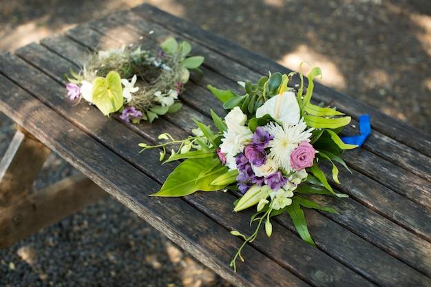 Buquê de casamento e grinalda em uma mesa de madeira