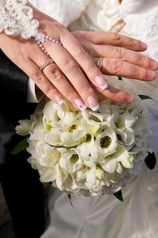 Buquê de casamento e mãos com anéis flores brancas