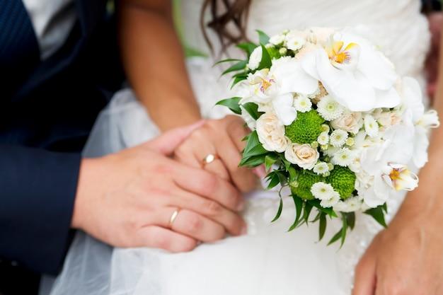Buquê de casamento e mãos com anéis
