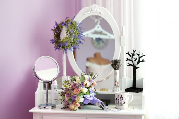 Buquê de casamento e xícara de chá na mesa de cabeceira com espelho