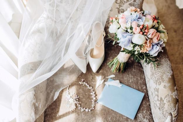 Buquê de casamento elegante com fita, convites de casamento, anéis de noivado e sapatos para a noiva em uma cadeira.