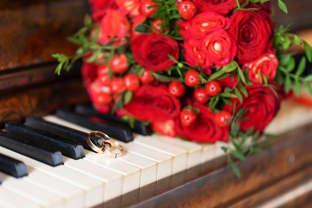 Buquê de casamento elegante de rosas vermelhas no piano. detalhes do casamento.