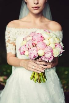 Buquê de casamento elegante nas mãos da noiva. buquê de peônias brancas e rosa. buquê com fita branca. mão da noiva com um anel de casamento.