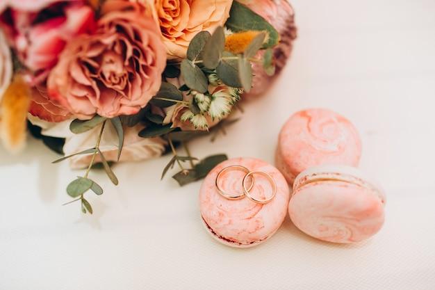 Buquê de casamento em cores de outono, alianças e biscoitos em uma mesa branca.