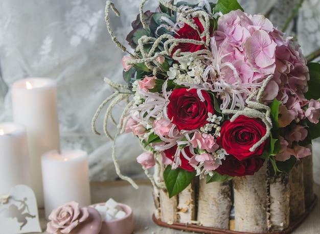 Buquê de casamento em um pedaço de madeira com velas brancas