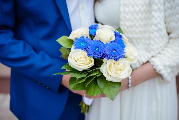 Buquê de casamento fechar nas mãos da noiva e do noivo