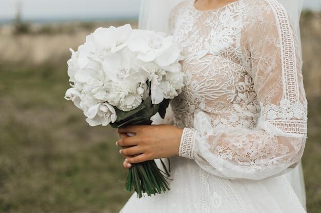 Buquê de casamento feito de peônias brancas na mão da noiva ao ar livre