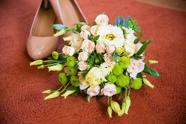 Buquê de casamento lindo e sapatos no chão