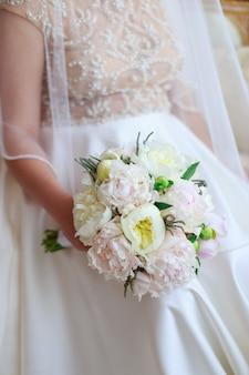 Buquê de casamento lindo na mão da noiva de peônias brancas