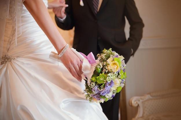 Buquê de casamento na mão da noiva com o noivo