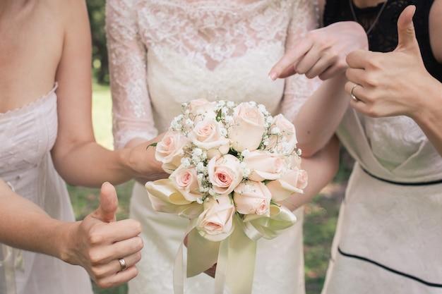 Buquê de casamento nas mãos da mulher. noiva e damas de honra mostram sinal de ok e polegar para cima