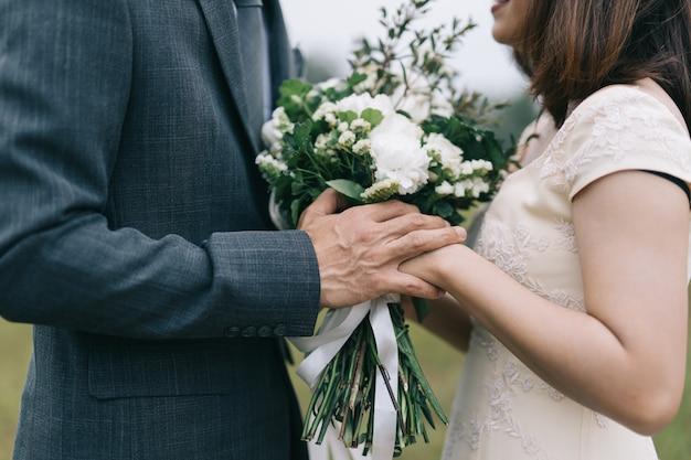 Buquê de casamento nas mãos da noiva e do noivo no fundo de um córrego da montanha.