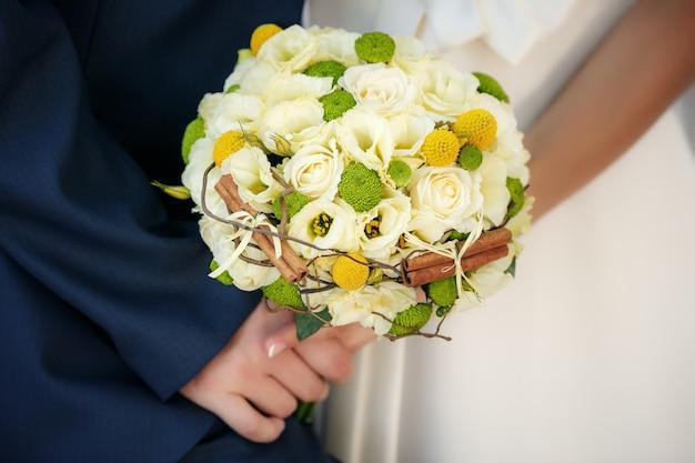Buquê de casamento nas mãos da noiva e do noivo