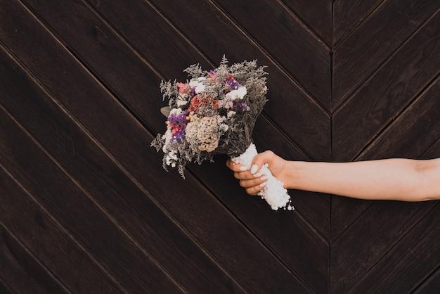 Buquê de casamento nas mãos da noiva em uma prancha de madeira