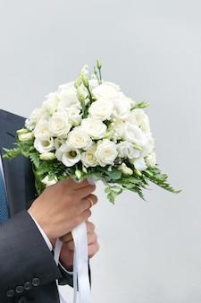 Buquê de casamento nas mãos do noivo