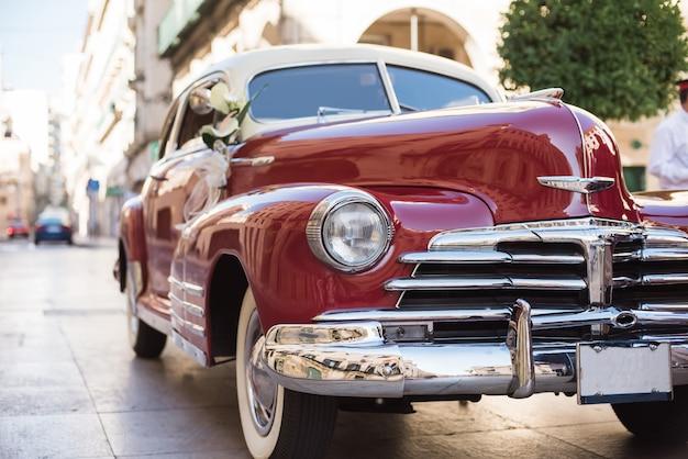 Buquê de casamento no carro de noiva vintage vermelho.