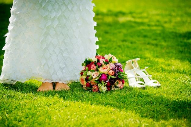 Buquê de casamento perto de seus pés e sapatos na grama verde