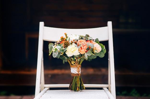 Buquê de casamento rústico e delicados sapatos de noiva em uma cadeira branca.