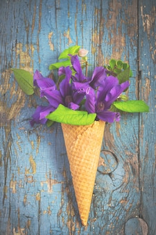 Buquê de clematis azul no cone de waffle de sorvete