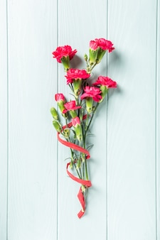 Buquê de cravo-de-rosa sobre fundo claro de madeira turquesa