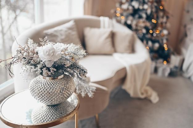 Buquê de decoração de natal em um vaso de prata na mesa de cabeceira de vidro contra um sofá branco e árvore de natal decorada com luzes de guirlanda