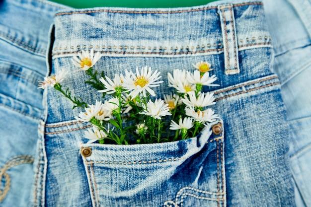 Buquê de flor branca no bolso de uma calça jeans
