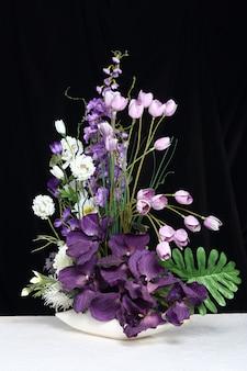 Buquê de flor roxa artificial colorido, mesa de fundo branco preto