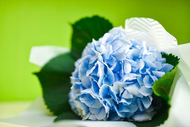 Buquê de flores azuis sobre um fundo verde