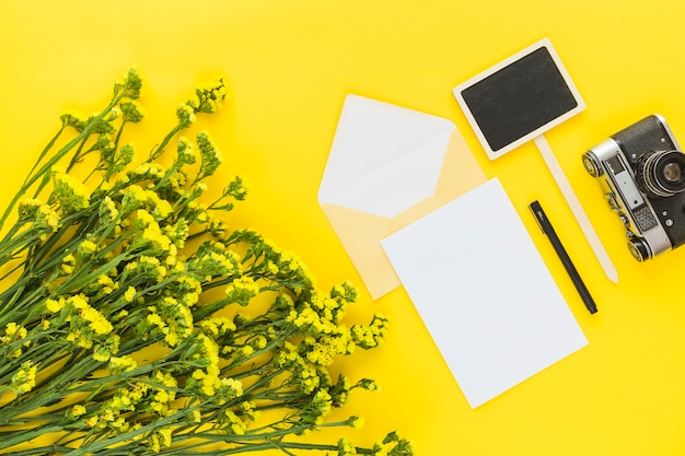 Buquê de flores bonitas; cartão; envelope; caneta; câmera e letreiro sobre fundo amarelo