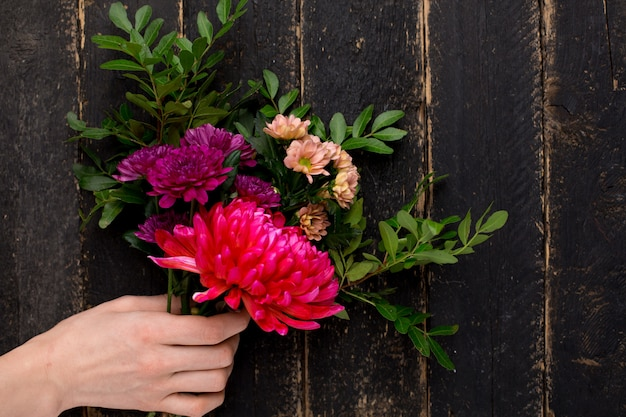 Buquê de flores bonitas para o feriado em uma mão feminina em madeira