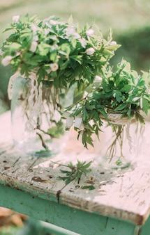 Buquê de flores brancas da primavera em frasco de vidro na cadeira de madeira na floresta ao ar livre