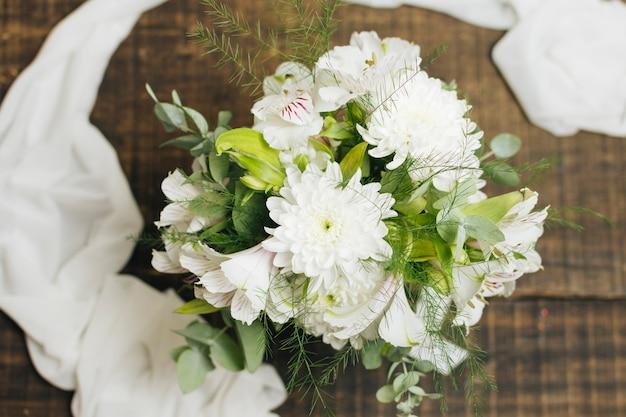 Buquê de flores brancas decorativas com cachecol na mesa de madeira