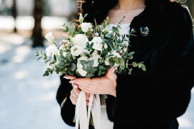 Buquê de flores brancas e folhagens nas mãos da noiva no inverno de fundo.