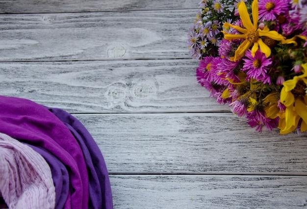 Buquê de flores brilhantes de outono e pilha de lenços, formando um quadro