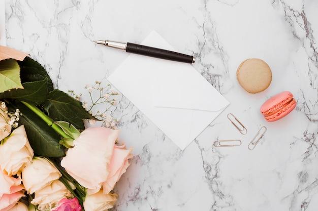 Buquê de flores; caneta tinteiro; envelope; clipe de papel e macaroons no fundo texturizado em mármore