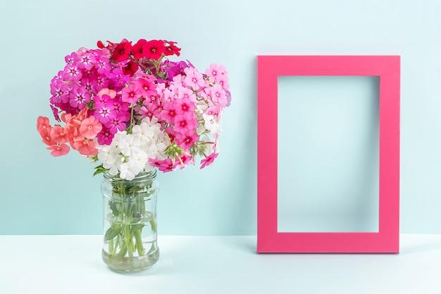 Buquê de flores coloridas brilhantes em um vaso e uma moldura vazia de madeira na mesa no contexto da parede azul.